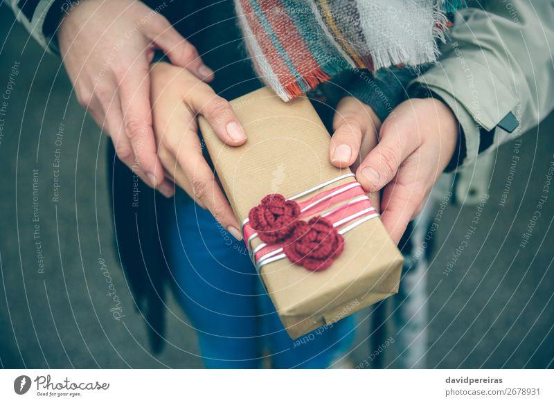 Frauen- und Männerhände mit Geschenkbox im Außenbereich Lifestyle Glück Winter Feste & Feiern Geburtstag Mensch Erwachsene Mann Paar Hand Herbst Blume Straße