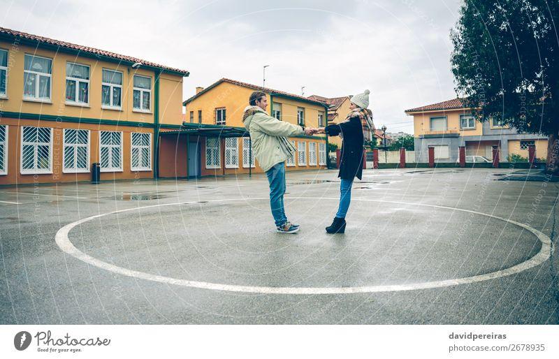 Paar hält Hände innerhalb des Kreises, der auf den Boden gemalt ist. Lifestyle Glück schön Freizeit & Hobby Winter Mensch Frau Erwachsene Mann Freundschaft Arme