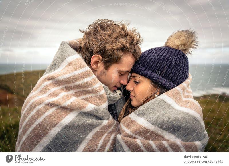 Junges Paar, das sich an einem kalten Tag unter der Decke im Freien umarmt. Lifestyle schön Meer Winter Berge u. Gebirge Frau Erwachsene Mann Natur Himmel