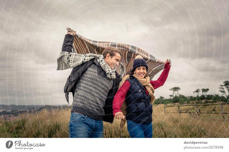 Junges Paar, das an einem windigen Tag im Freien mit Decke spielt. Lifestyle Glück schön Spielen Meer Winter Berge u. Gebirge Frau Erwachsene Mann Natur Himmel