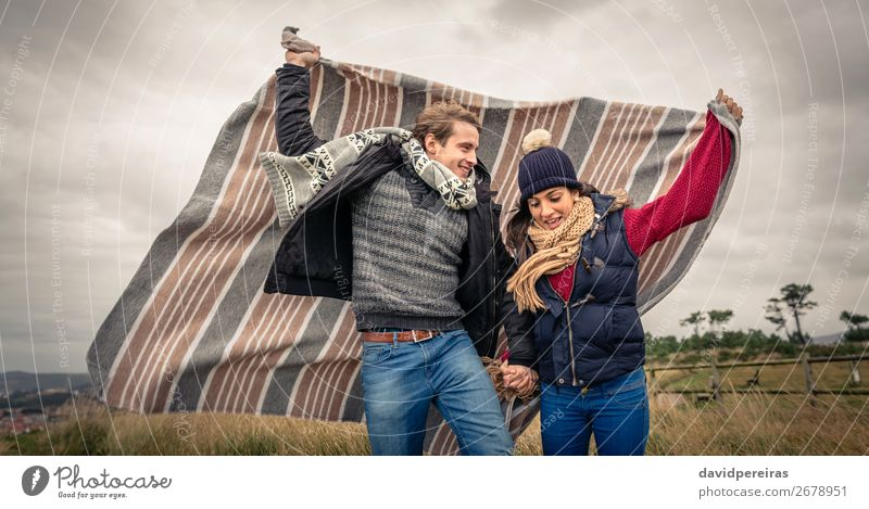 Junges Paar, das an einem windigen Tag im Freien mit Decke spielt. Lifestyle Freude Glück schön Spielen Freiheit Winter Berge u. Gebirge Frau Erwachsene Mann