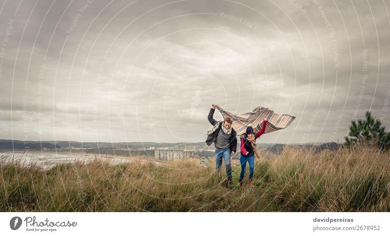 Junges Paar, das an einem windigen Tag im Freien mit Decke spielt. Lifestyle Freude Glück schön Spielen Meer Winter Berge u. Gebirge Frau Erwachsene Mann Natur