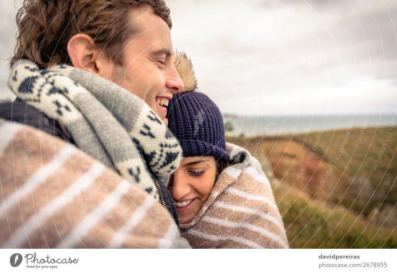 Junges Paar, das an einem kalten Tag unter der Decke im Freien lacht. Lifestyle Glück schön Meer Winter Berge u. Gebirge Frau Erwachsene Mann Natur Himmel