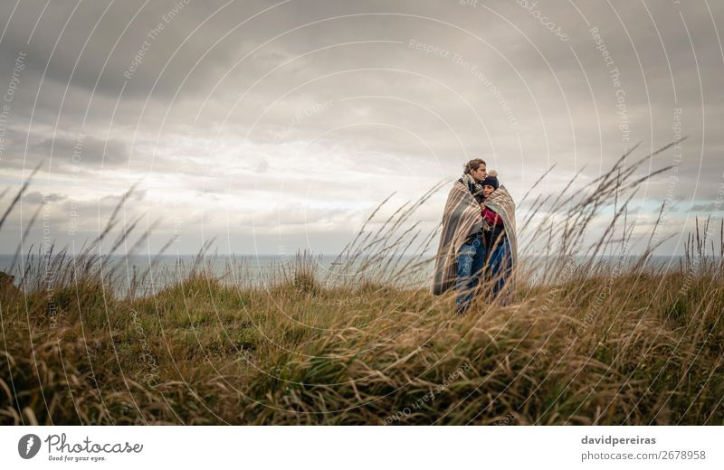 Junges Paar, das sich an einem kalten Tag unter der Decke im Freien umarmt. Lifestyle Glück schön Meer Winter Berge u. Gebirge Frau Erwachsene Mann Natur Himmel