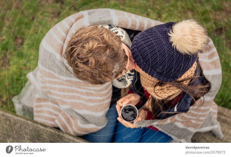 Junges Paar unter der Decke mit heißem Getränk, das sich im Freien küsst. Kaffee Tee Lifestyle Abenteuer Winter Tisch Frau Erwachsene Mann Hand Natur Herbst