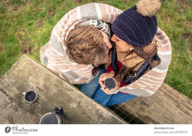 Junges Paar unter der Decke mit heißem Getränk, das sich im Freien küsst. Kaffee Tee Lifestyle Glück Winter Tisch Frau Erwachsene Mann Hand Natur Herbst Wind