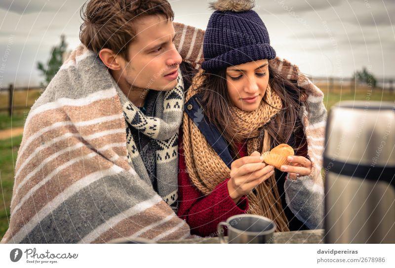 Junges Paar unter der Decke isst Muffin im Freien an einem kalten Tag. Essen Getränk Kaffee Tee Lifestyle Glück Meer Winter Tisch Frau Erwachsene Mann Natur