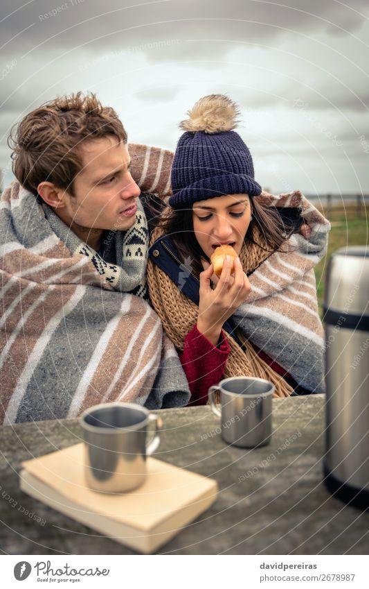 Junges Paar unter der Decke isst Muffin im Freien an einem kalten Tag. Essen Getränk Kaffee Tee Lifestyle Abenteuer Meer Winter Tisch Frau Erwachsene Mann Natur