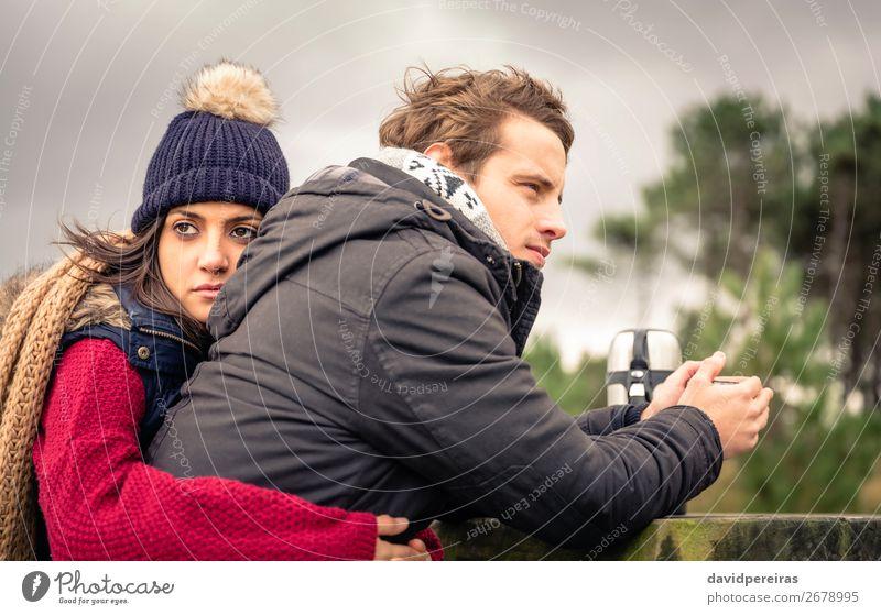 Junges Paar, das sich umarmt und ein heißes Getränk im Freien genießt. Kaffee Tee Lifestyle Glück Meer Winter Berge u. Gebirge Frau Erwachsene Mann Hand Natur