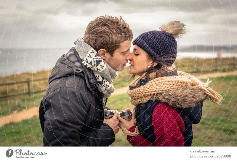 Junges Paar, das sich küsst und Tassen mit heißen Getränken im Freien hält. Kaffee Lifestyle Glück Meer Winter Berge u. Gebirge Frau Erwachsene Mann Hand Natur