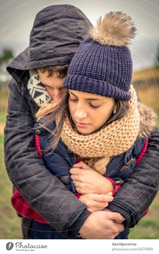 Junges Paar mit Hut und Schal, das sich im Freien umarmt. Lifestyle Glück schön Winter Frau Erwachsene Mann Natur Himmel Wolken Herbst Wind Wärme Bekleidung