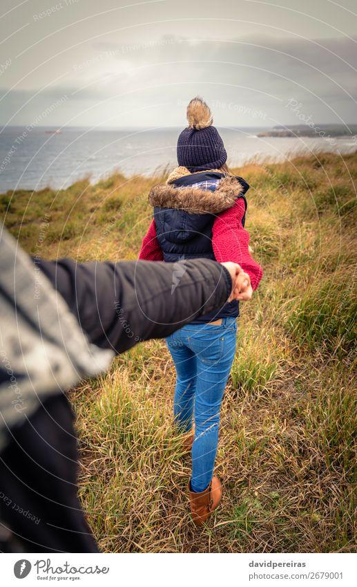 Junge Frau, die die Hand des Mannes hält und von einer Wiese führt. Lifestyle Glück schön Meer Winter Erwachsene Paar Natur Himmel Wolken Herbst Wind Küste