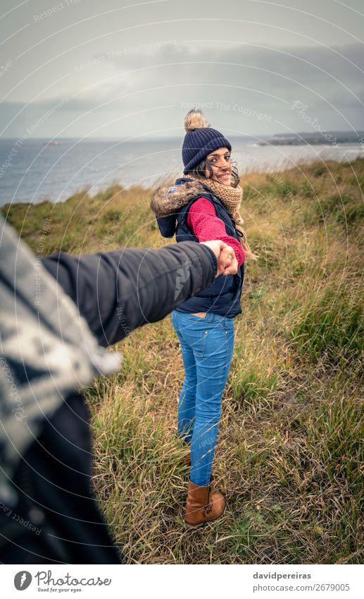 Junge Frau, die die Hand des Mannes hält und von einer Wiese führt. Lifestyle Glück schön Abenteuer Meer Winter Erwachsene Paar Natur Himmel Wolken Herbst Wind