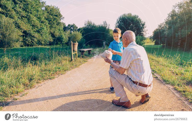 Großvater zeigt seinen Hut dem Enkelkind im Freien. Lifestyle Freude Glück Freizeit & Hobby Spielen Sommer Kind Junge Mann Erwachsene Eltern