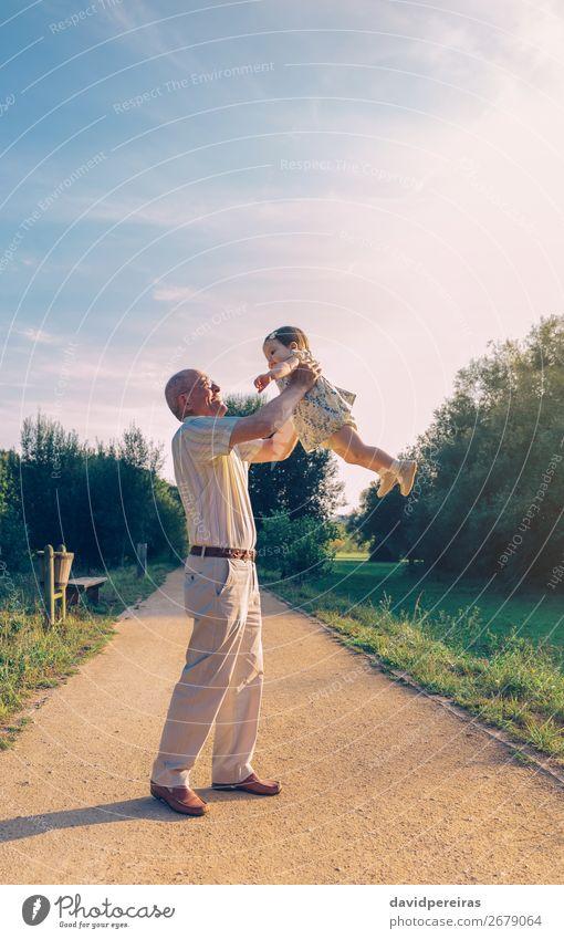 Senior Mann spielt mit einem kleinen Mädchen im Freien. Lifestyle Glück Erholung Freizeit & Hobby Spielen Sommer Mensch Baby Kleinkind Frau Erwachsene Eltern