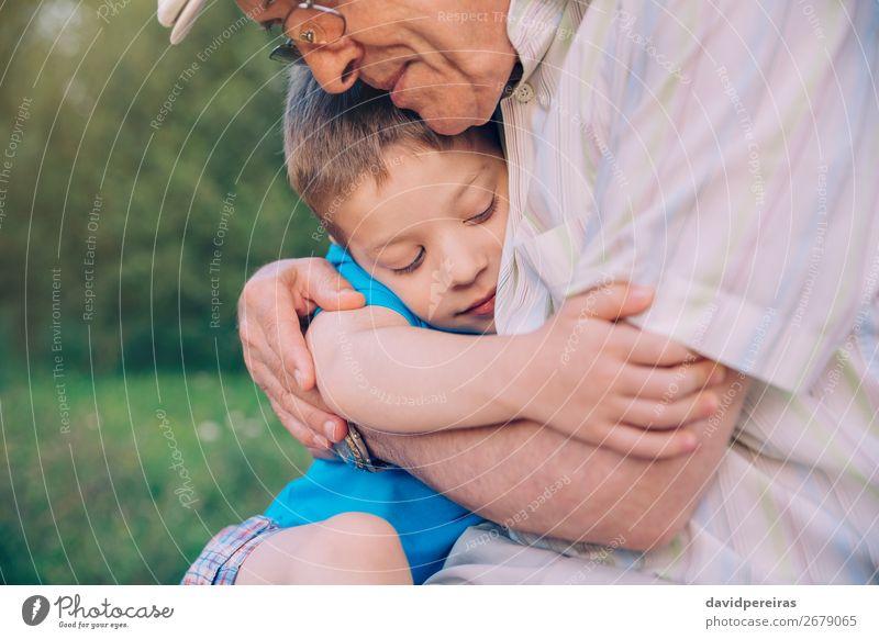 Glücklicher Enkel umarmt Großvater vor dem Hintergrund der Natur im Freien Lifestyle Erholung Freizeit & Hobby Sommer Garten Kind Mensch Junge Mann Erwachsene