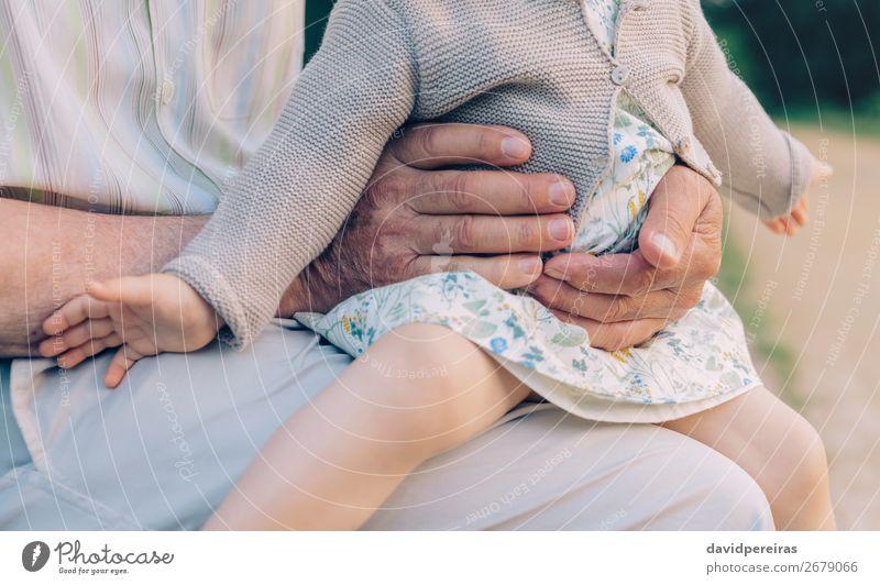 Kleines Mädchen sitzt auf den Beinen des älteren Mannes im Freien. Haut Leben Kind Ruhestand Mensch Baby Frau Erwachsene Eltern Großvater