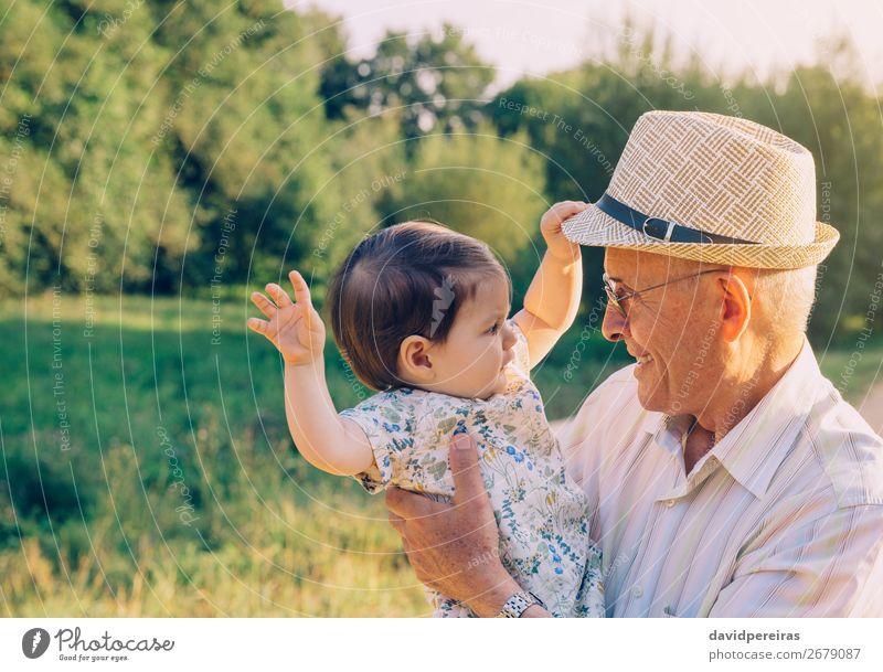 Kleines Mädchen spielt mit dem Hut eines älteren Mannes im Freien. Lifestyle Glück Erholung Spielen Sommer Mensch Baby Kleinkind Frau Erwachsene Eltern