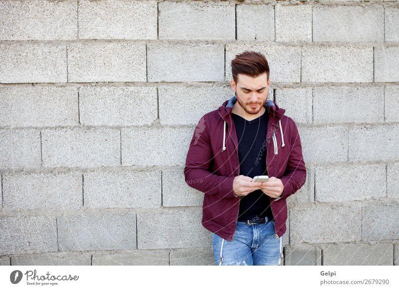 Cooler junger Mann mit Bart, der wie ein Handy aussieht. Lifestyle Stil Sommer Mensch Erwachsene Straße Mode Jeanshose Piercing Vollbart Coolness Erotik trendy