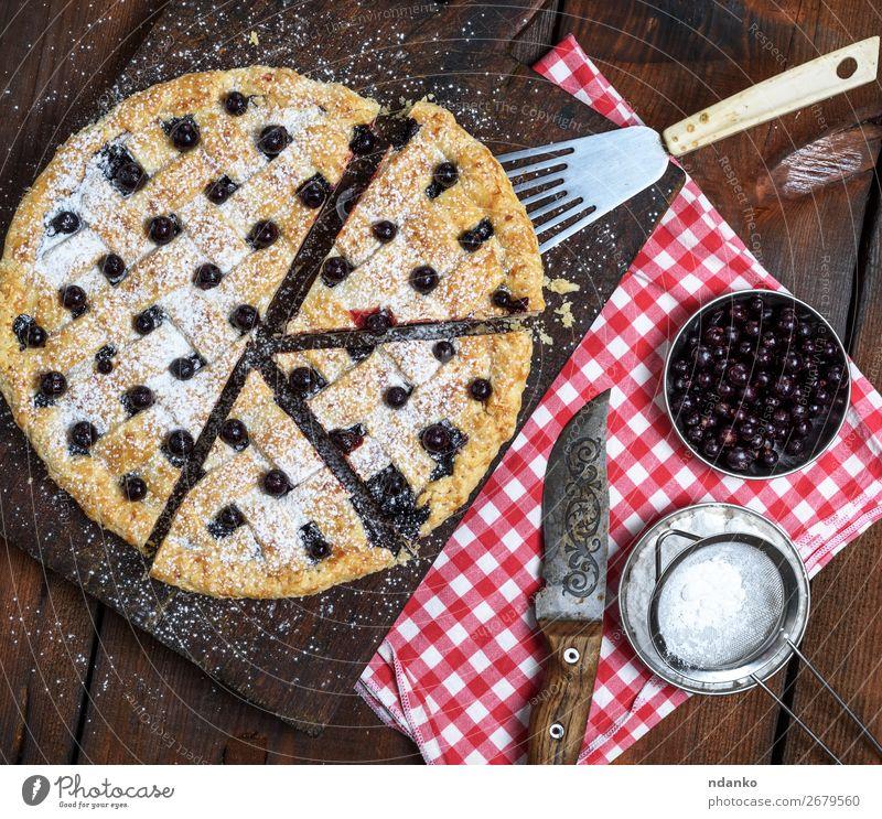 gebackener runder schwarzer Johannisbeerkuchen in Stücke geschnitten Frucht Teigwaren Backwaren Kuchen Dessert Süßwaren Ernährung Tisch Holz frisch lecker oben