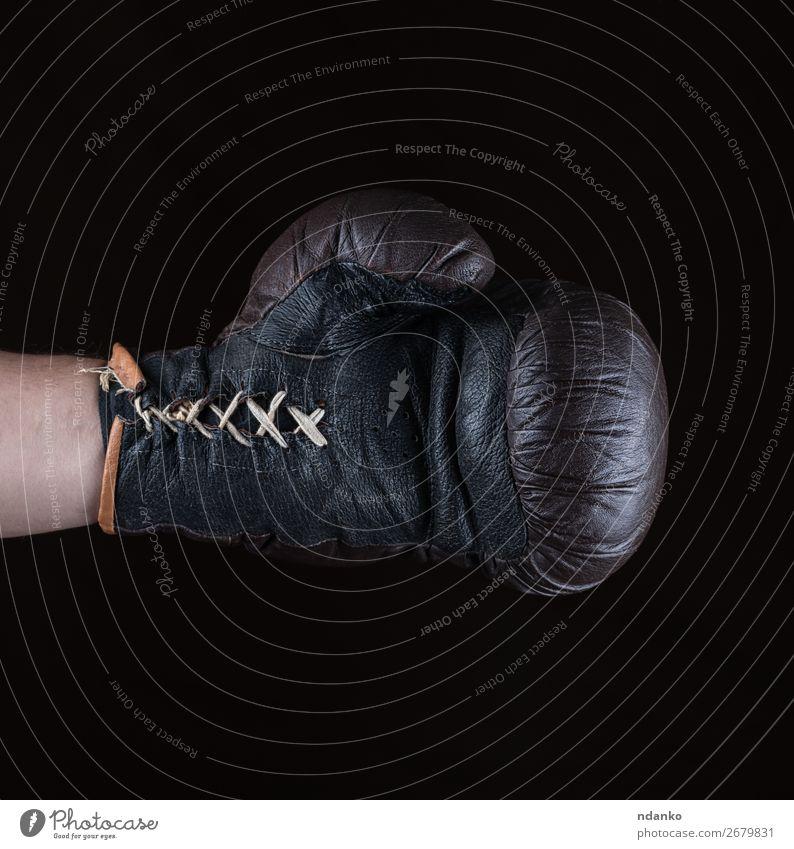 brauner Boxhandschuh angezogen auf der Männerhand Fitness Sport Erfolg Hand Leder Handschuhe alt dreckig schwarz Kraft Schutz Konkurrenz Kasten Boxer Boxsport
