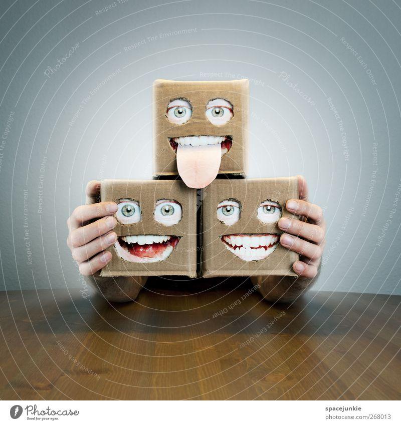 Künstlertrio beobachten Lächeln lachen schreien Blick leuchten außergewöhnlich gruselig klein trashig Karton Gesicht Auge Mund Tisch Roboter 3 verrückt surreal