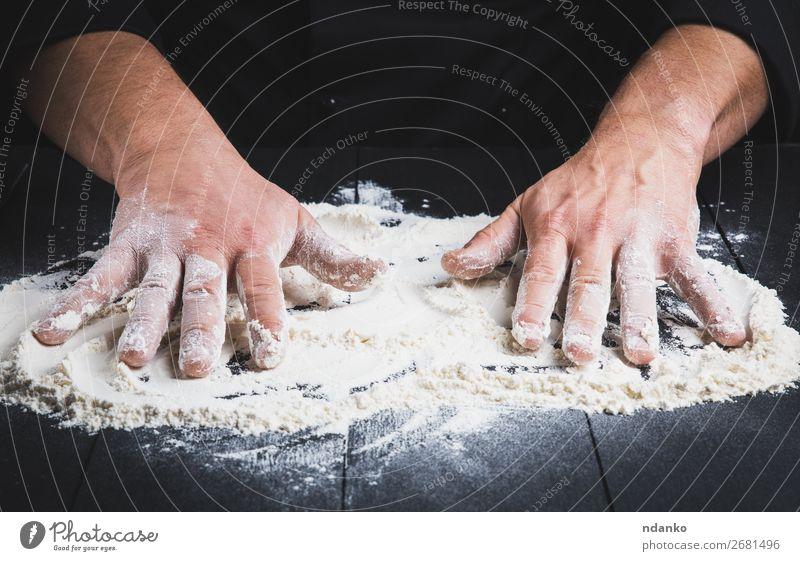 weißes Weizenmehl auf einem schwarzen Holztisch Teigwaren Backwaren Brot Tisch Küche Koch Mensch Mann Erwachsene Hand machen dunkel Mehl Küchenchef Pizza