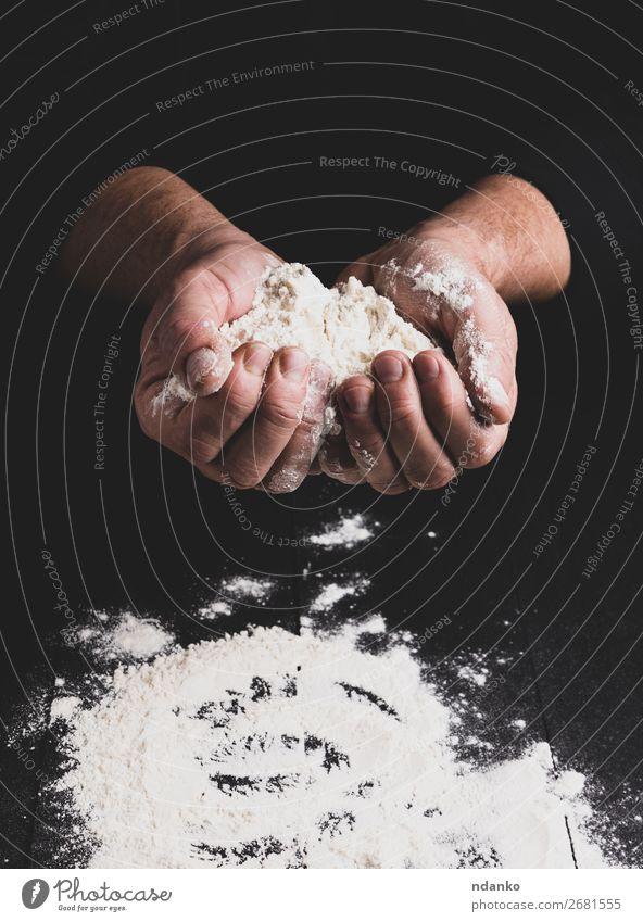 weißes Weizenmehl in männlichen Händen, schwarzer Hintergrund Teigwaren Backwaren Brot Tisch Küche Mensch Hand Holz machen dunkel Mehl Pizza Bäckerei gebastelt