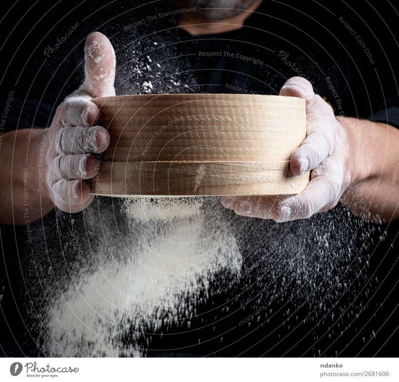 Mann siebt weißes Weizenmehl durch ein Holzsieb. Teigwaren Backwaren Brot Ernährung Küche Koch Mensch Erwachsene Hand Sieb Bewegung machen frisch schwarz Mehl