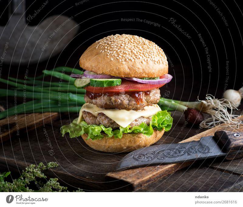 Cheeseburger mit Gemüse Fleisch Käse Brot Brötchen Mittagessen Abendessen Fastfood Messer Tisch Restaurant Holz dunkel frisch groß lecker grün schwarz