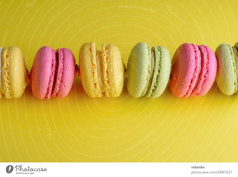 Dessert Makronen liegt in der Mitte in einer Reihe. Kuchen Süßwaren hell gelb grün rosa Farbe Mandel Hintergrund backen Bäckerei Biskuit farbenfroh Sahne