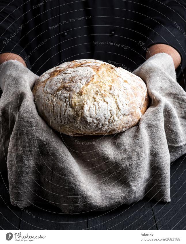 gebackenes rundes hausgemachtes Brot auf einer grauen Serviette Ernährung Tisch Küche Koch Mensch Hand Holz Essen machen dunkel frisch braun schwarz weiß