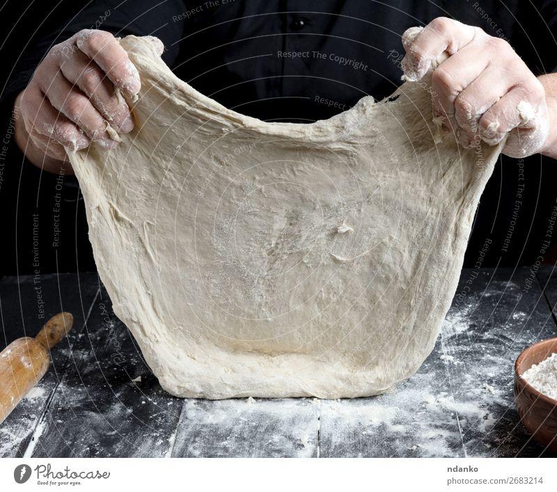 Koch in schwarzer Jacke, Knetteig Teigwaren Backwaren Brot Ernährung Tisch Küche Mensch Mann Erwachsene Hand Holz machen weiß Tradition backen Bäcker Bäckerei