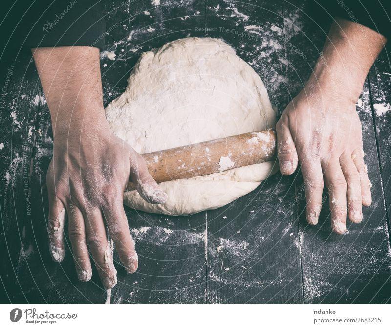 Chefkoch in einer schwarzen Tunika rollt einen Teig für eine runde Pizza. Teigwaren Backwaren Brot Ernährung Tisch Küche Mensch Mann Erwachsene Hand Holz machen