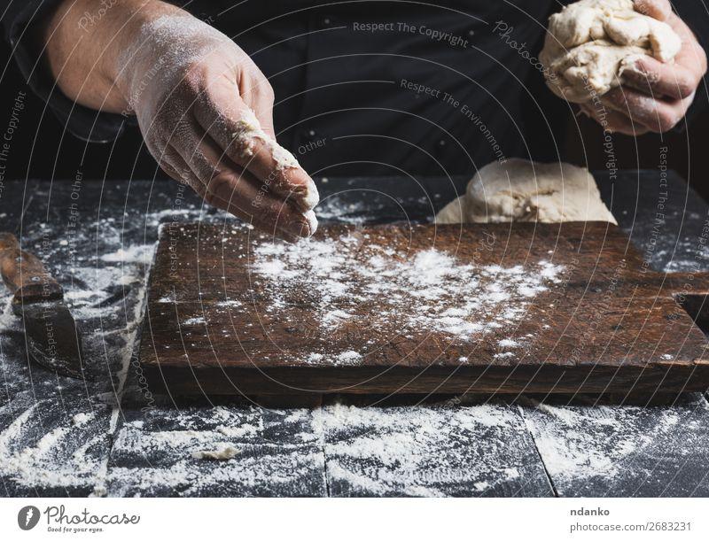 Koch in schwarzer Jacke knet Teig Teigwaren Backwaren Brot Ernährung Haut Tisch Küche Mensch Mann Erwachsene Hand Holz machen weiß Tradition backen Bäcker