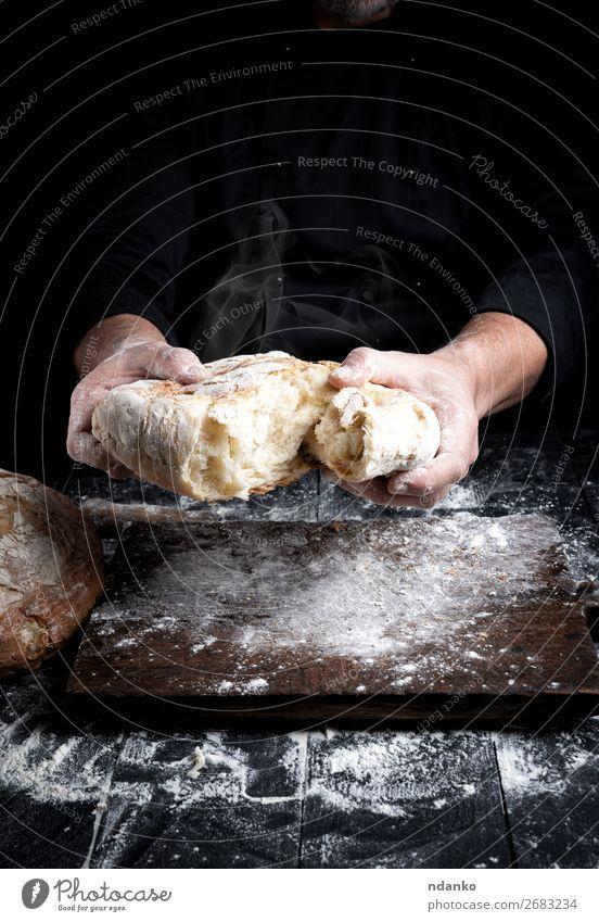 gebackenes Brot Ernährung Tisch Küche Koch Mensch Hand 30-45 Jahre Erwachsene Holz machen dunkel frisch heiß braun schwarz weiß Tradition Bäcker Bäckerei