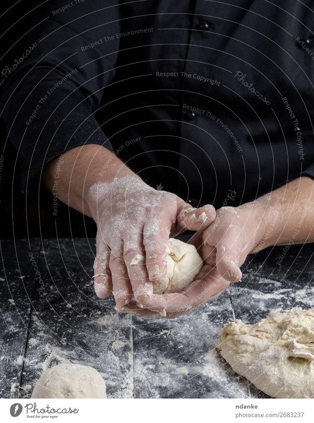 kochen und Teigkugeln auf einem schwarzen Holztisch zubereiten. Teigwaren Backwaren Brot Ernährung Haut Tisch Küche Mensch Mann Erwachsene Hand machen weiß