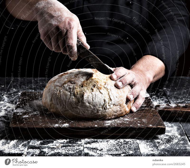 Mann schneidet mit einem Messer einen runden ganzen Laib. Brot Ernährung Tisch Küche Mensch Hand Finger Holz machen dunkel frisch braun schwarz weiß Tradition