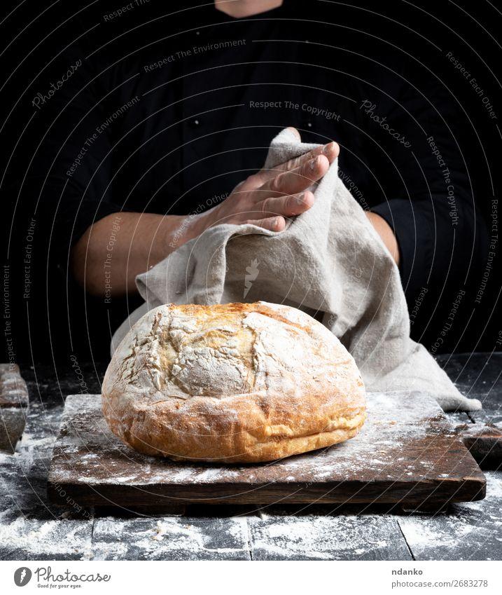 gebackenes Rundbrot Brot Ernährung Tisch Küche Koch Hand Finger Holz Essen machen dunkel frisch braun schwarz weiß Tradition Bäckerei Holzplatte
