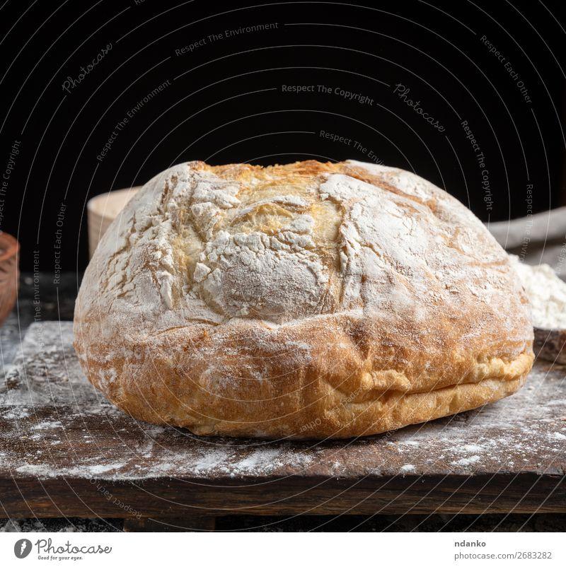 ganzes gebackenes Rundbrot Brot Ernährung Tisch Küche Holz machen dunkel frisch braun schwarz weiß Tradition Bäckerei Holzplatte Essen zubereiten Schneidebrett