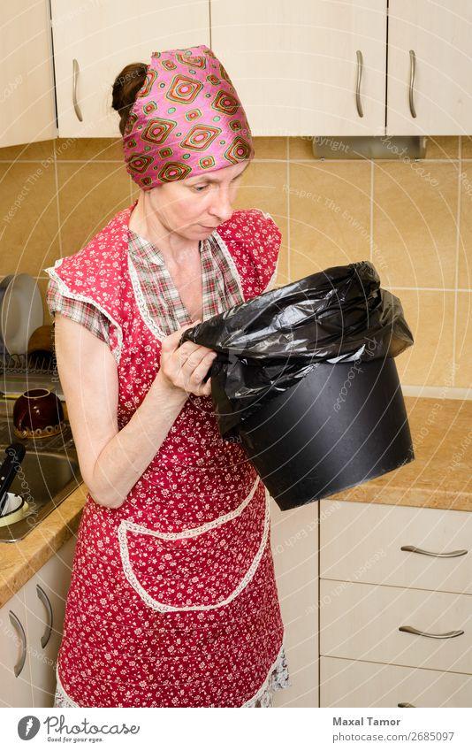 Frau, die in einen Mülleimer schaut. Lifestyle Küche Mensch Erwachsene Dose Kunststoff beobachten tragen schlecht schlechter Geruch Tasche Behälter Kaukasier