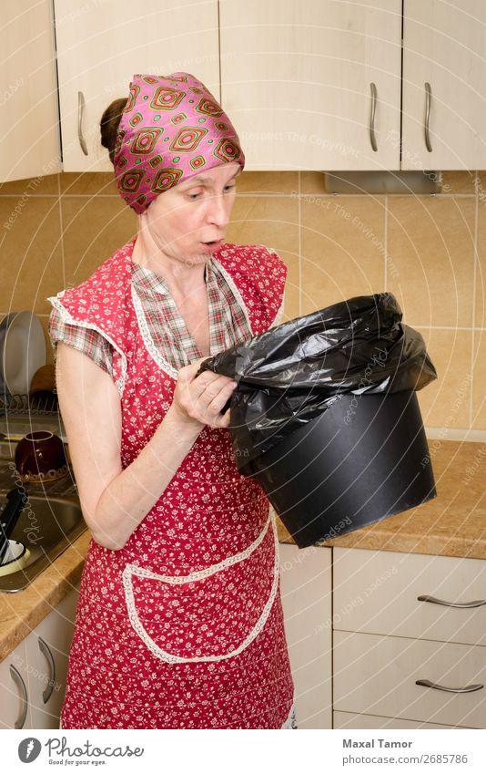 Frau, die in einen Mülleimer schaut. Lifestyle Küche Mensch Erwachsene Schal Dose Kunststoff beobachten tragen Schürze schlecht schlechter Geruch Tasche