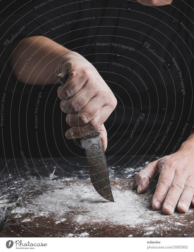 Koch in schwarzer Kleidung mit einem alten alten Messer Teigwaren Backwaren Brot Tisch Küche Mensch Hand Finger Holz machen braun Bäckerei Küchenchef gebastelt