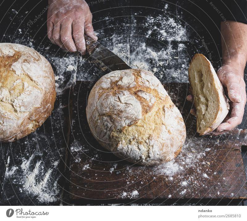 Mann schneidet gebackenes Rundbrot auf einem braunen Holzbrett. Brot Ernährung Tisch Küche Mensch Hand Finger machen dunkel frisch schwarz weiß Tradition ganz