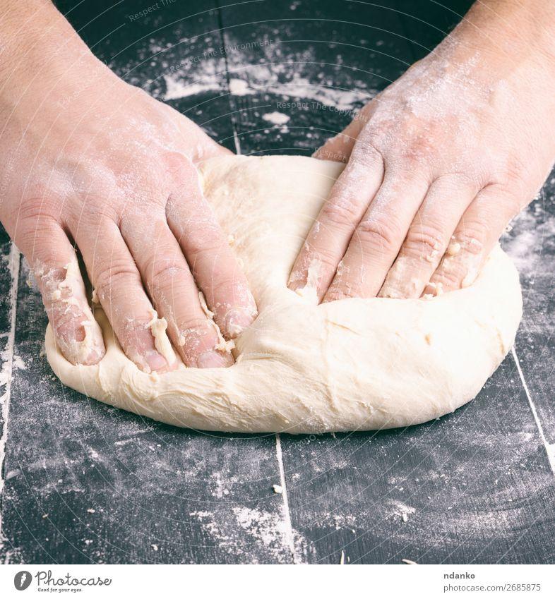 männliche Hände ersetzen weißen Weizenmehlteig Teigwaren Backwaren Brot Ernährung Tisch Küche Mann Erwachsene Hand Holz machen schwarz Tradition backen Bäcker