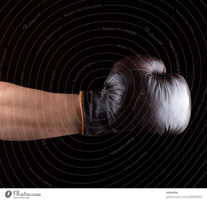 Hand trägt einen braunen Leder-Boxhandschuh. Sport Erfolg Handschuhe alt Fitness dreckig dunkel schwarz Kraft Schutz Konkurrenz Hintergrund Kasten Boxer