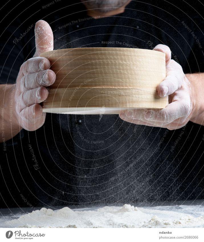 rundes Holzsieb in männlichen Händen Teigwaren Backwaren Brot Ernährung Tisch Küche Mensch Mann Erwachsene Hand 1 30-45 Jahre Sieb Bewegung machen dunkel frisch