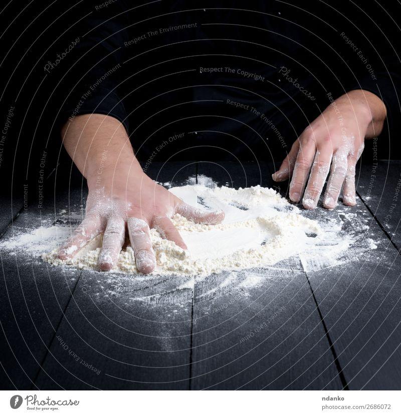 weißes Weizenmehl auf einem schwarzen Holztisch Teigwaren Backwaren Brot Tisch Küche Koch Mensch Mann Erwachsene Hand machen dunkel frisch kneten Bäcker
