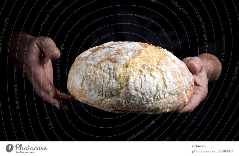 Kochhände halten einen ganzen Laib gebackenes Rundbrot. Brot Ernährung Küche Mensch Hand 30-45 Jahre Erwachsene machen dunkel frisch braun schwarz weiß
