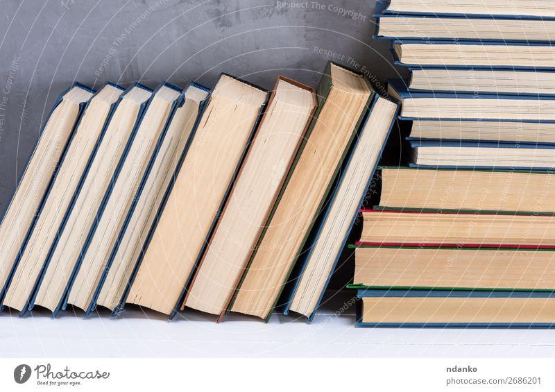 Stapel verschiedener Bücher auf dem Tisch lesen Wissenschaften Schule Klassenraum Studium Buch Bibliothek Papier gelb grau weiß Weisheit Idee Hintergrund